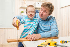 Father teaches his son to cut the wooden plank Stock Photos