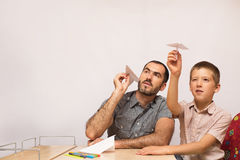 Father teaches his son to do paper airplanes. Indoor royalty free stock photography