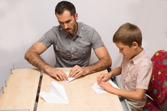 Father teaches his son to do paper airplanes. Indoor royalty free stock images