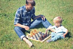Father teaches his son to play chess. Dad and son time together. Father teaches his child to play chess. Dad and son time together outdoor stock photography