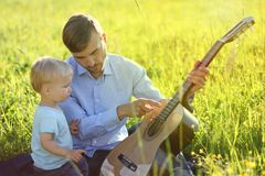 Father teaches his son to play guitar. Time together dad and son. Outdoor royalty free stock photography