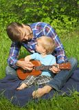 Father teaches his son to play ukulele. Time together dad and son outdoor.  stock photography