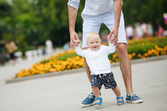 The father teaches his son to walk. Royalty Free Stock Photo