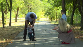 Father teaches his son walk stock footage