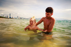 Father teaches little daughter to swim in shallow sea water Royalty Free Stock Images