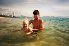 Father teaches little daughter to swim in shallow sea water Stock Images