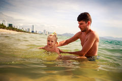 Father teaches little daughter to swim in shallow sea water Royalty Free Stock Photos