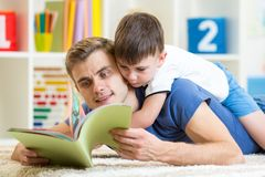 Father teaches reading book to kid royalty free stock photography