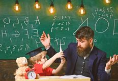 Father teaches son elementary knowledge, discuss, explain. Grade school concept. Kid studies with teacher, listening. With attention. Teacher and pupil in stock image
