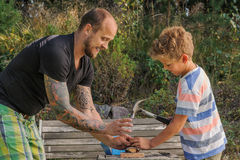 Father teaches son how to hammer a nail royalty free stock photos