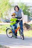 Father teaches son how to ride a bicycle. In city park stock image