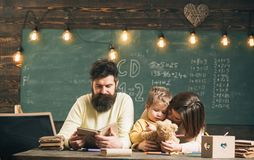 Father teaches son, reading book, while mother play with toy, chalkboard on background. Boy listening mom with attention. Homeschooling concept. Family cares Stock Images