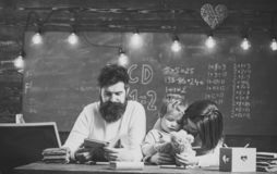 Father teaches son, reading book, while mother play with toy, chalkboard on background. Boy listening mom with attention. Homeschooling concept. Family cares royalty free stock photo