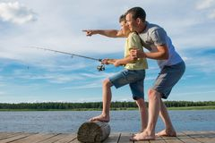 Father teaches son to fish on the pier, against the blue sky royalty free stock images