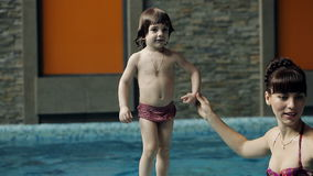 Father teaches son to swim in the pool. stock footage