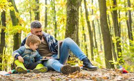 Father teaches son use modern technology. United with nature. Ecology lesson. Forest school and ecology education. Man. Bearded father and little son with royalty free stock image