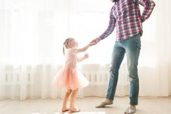 Father teaches to dance his cute little daughter. stock photos