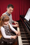 Father teaches young daughter playing piano. Piano player and his little girl student during lesson Royalty Free Stock Images