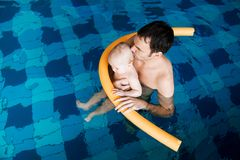 Smiling charming baby in swimming pool. Father teaching baby to swim. Portrait of a charming 11 months child in the classroom in a swimming pool. Healthy Family Stock Photography