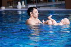 Smiling charming baby in swimming pool. Father teaching baby to swim. Portrait of a charming 11 months child in the classroom in a swimming pool. Healthy Family Royalty Free Stock Photos
