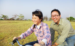 Father teaching child to ride bicycle. Happy Father teaching child to ride bicycle stock photography