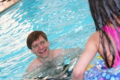 Father teaching child to swim. Smiling father in pool encouraging his daughter to swim into the pool royalty free stock photo