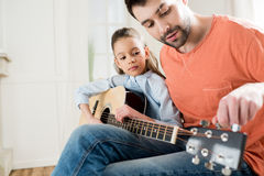 Father teaching concentrated little daughter playing guitar Stock Image