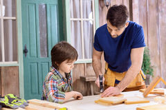 Father teaching concentrated son how to hammering nail in wooden plank Stock Photo