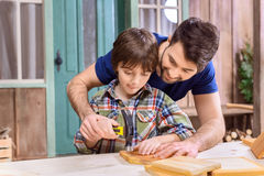 Father teaching concentrated son how to hammering nail in wooden plank Royalty Free Stock Photos