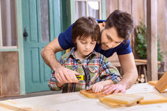 Father teaching concentrated son to hammering nail in wooden plank Royalty Free Stock Photos