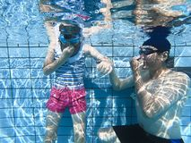 Father teaching daughter breathing in swimming pool stock photo
