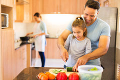 father teaching daughter cutting vegetables Stock Photos