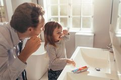 Father teaching daughter how to brush teeth. Father and daughter brushing teeth standing in bathroom. Man teaching his daughter how to brush teeth stock image