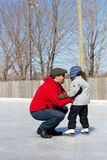 Father teaching daughter how to ice skate Royalty Free Stock Photos