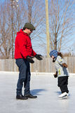Father teaching daughter how to ice skate Stock Images