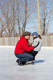 Father teaching daughter how to ice skate Royalty Free Stock Image
