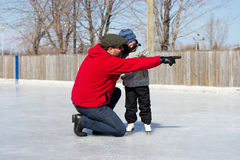 Father teaching daughter how to ice skate Royalty Free Stock Photography