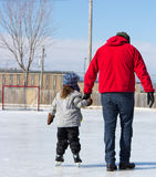 Father teaching daughter how to ice skate Stock Photography