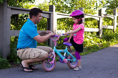 Father teaching daughter how to ride a bike Stock Photography