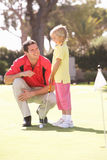Father Teaching Daughter To Play Golf. On Putting On Green Royalty Free Stock Photos