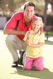 Father Teaching Daughter To Play Golf Royalty Free Stock Photography