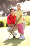 Father Teaching Daughter To Play Golf. On Putting On Green Stock Images