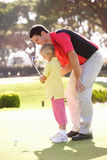 Father Teaching Daughter To Play Golf Royalty Free Stock Images