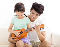 Father Teaching daughter To Play ukulele Royalty Free Stock Image