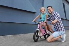 Father teaching daughter to ride bicycle. On street royalty free stock photography