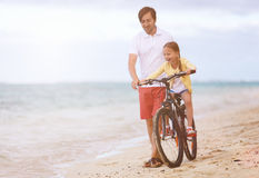 Father teaching daughter to ride bike Stock Photos