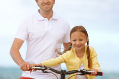 Father teaching daughter to ride bike Royalty Free Stock Photo