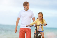 Father teaching daughter to ride bike Royalty Free Stock Images