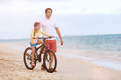 Father teaching daughter to ride bike Stock Photo