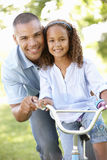 Father Teaching Daughter To Ride Bike In Park Royalty Free Stock Photos